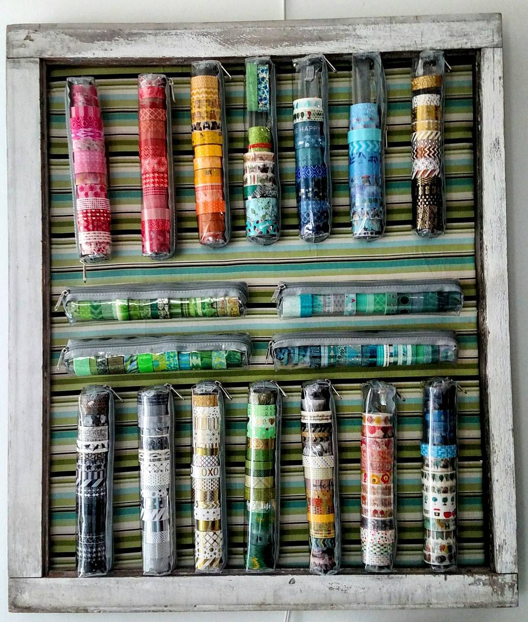 #washiTape frame made from a discarded window pane frame, 1/8″ board, fabric, and picture frame wire to hang it. The #washi tapes are stored in soft plastic zippered bags originally made for ribbon #craftstorage